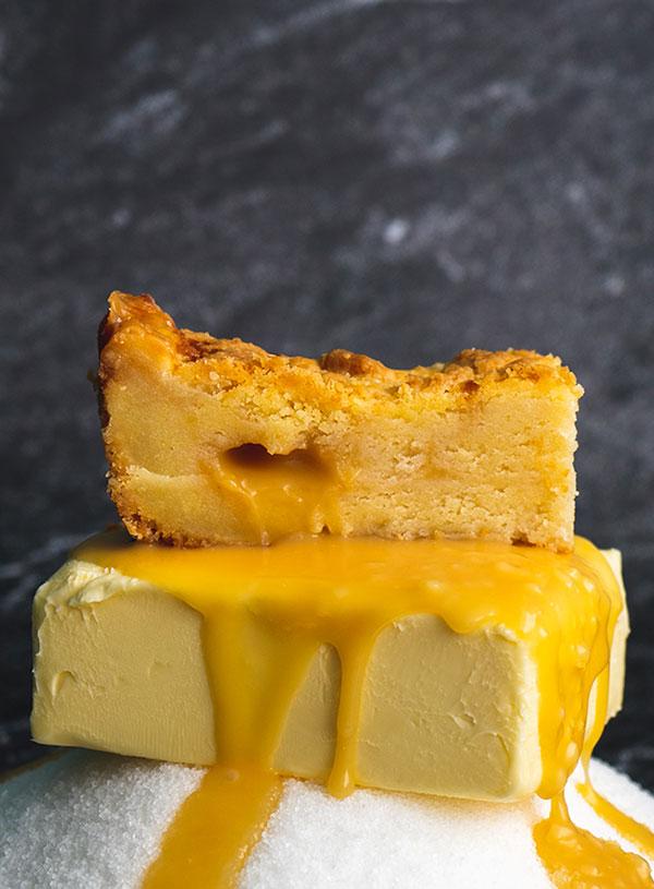 Salted caramel boterkoek op een homp boter op een berg van suiker waarover gezouten karamel saus druipt