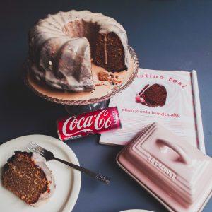 Cherry cola cake op een cake standaard, met erbij een plakje van de cake op een wit bordje, een roze botervloot en een tijdschrift opengeslagen op het recept.