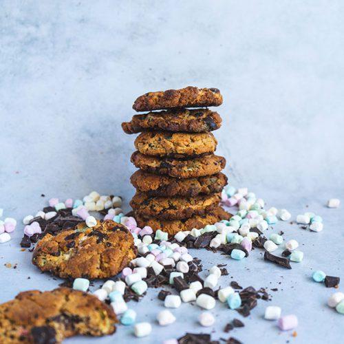Een stapel pindakaas smores koekjes op een witte achtergrond omringt door chocolade stukken en mini marshmallows