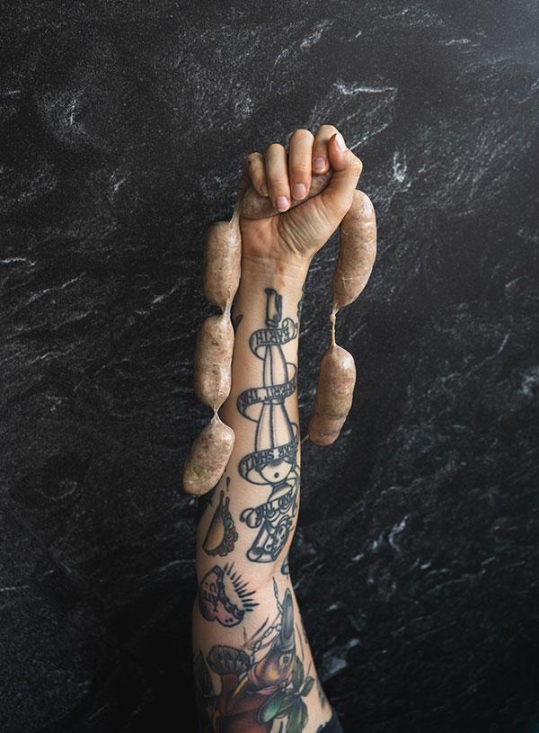 De getatoeëerde arm van Vette Sletten, die een streng rauw worsten in de lucht houdt.