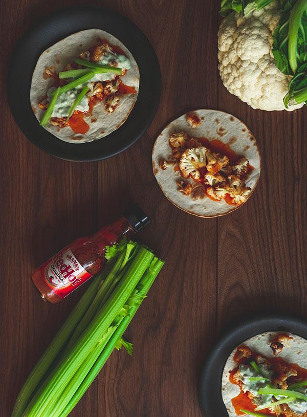 Een paar taco's met Buffalo bloemkool erop, met daarbij een bos bleekselderij, een fles hot sauce en een bloemkool.