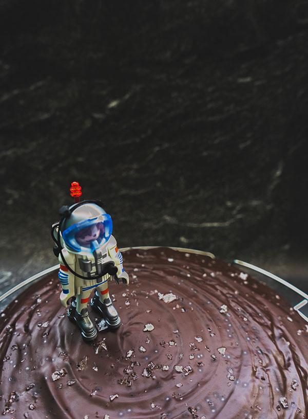 Een closeup van een playmobil astronaut die op een maan van chocoladecake landt.