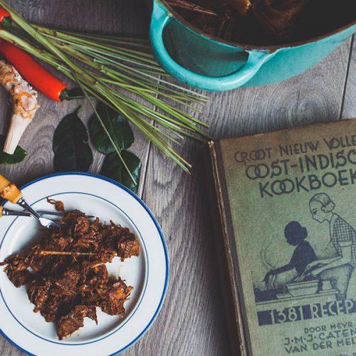 Een bord rendang met daarbij een koloniaal Indisch kookboek en eromheen wat losse ingrediënten