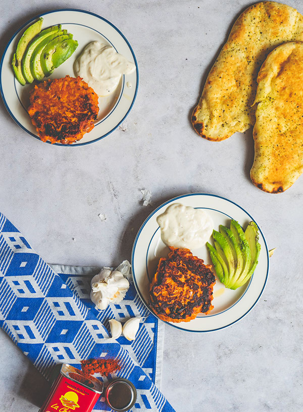 Twee borden met smoky zoete aardappelburgers met een waaier avocado en knoflook yogurt erbij, met daarnaast de ingrediënten en een paar naans.