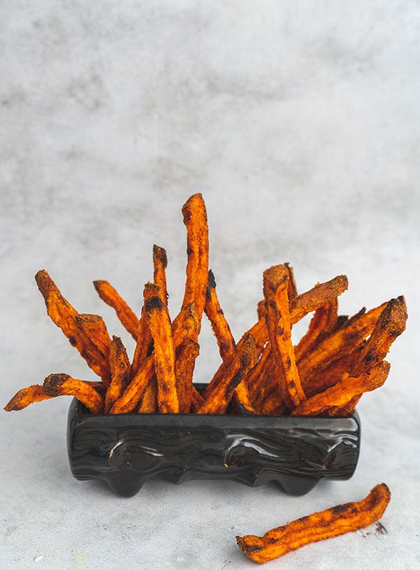 Een houtvormig keramiek bakje met zoete aardappelfrieten erin gestoken.