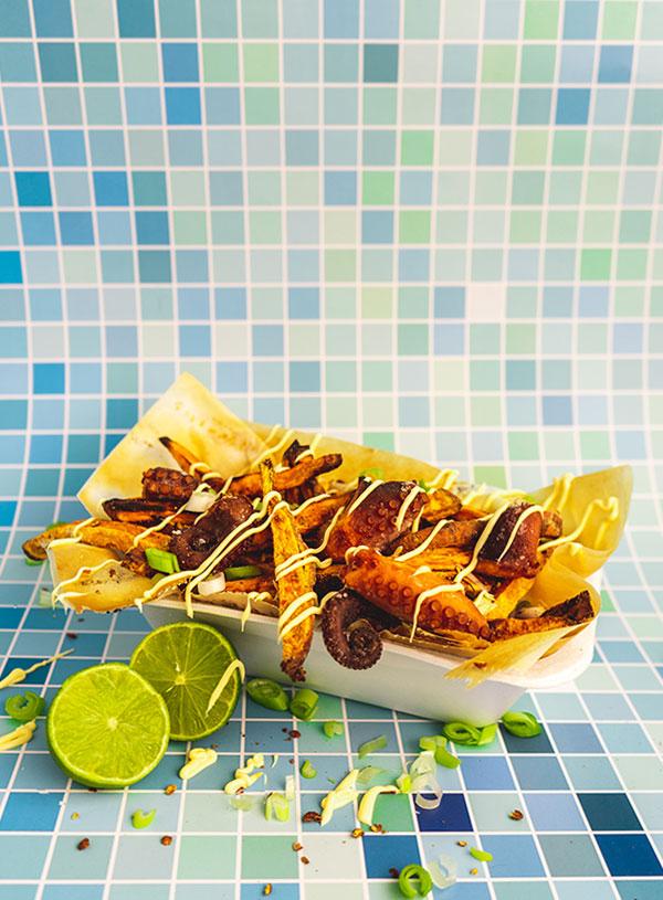 Een frietschaal met zoete aardappelfriet en gefrituurde octopus met daaroverheen slierten Kewpie mayonnaise en bosui en een gehalveerde limoen erbij.