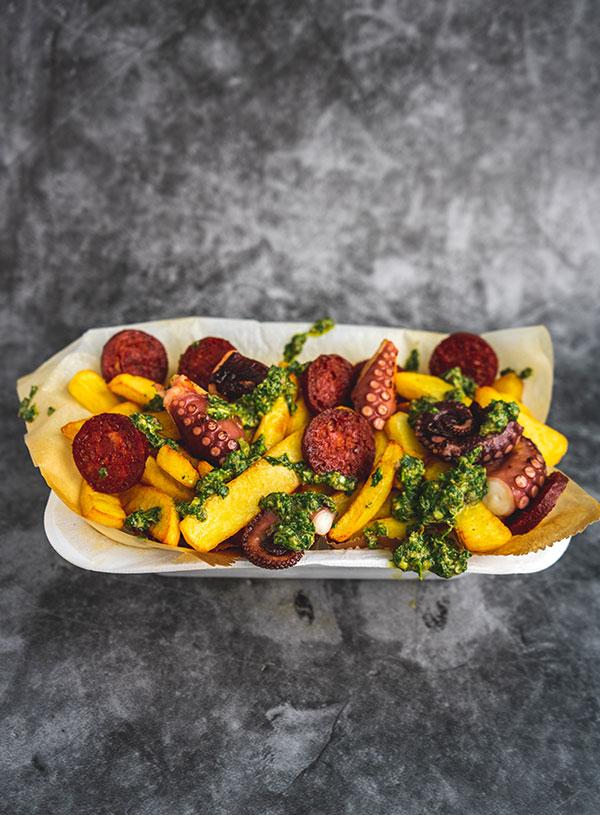 Een frietschaal met dikke frieten, gebakken octopus, gefrituurde chorizo en salsa verder erin.