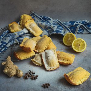 Madeleines bedekt met poedersuiker omringt door verse gember, een doorgesneden citroen en steranijs.