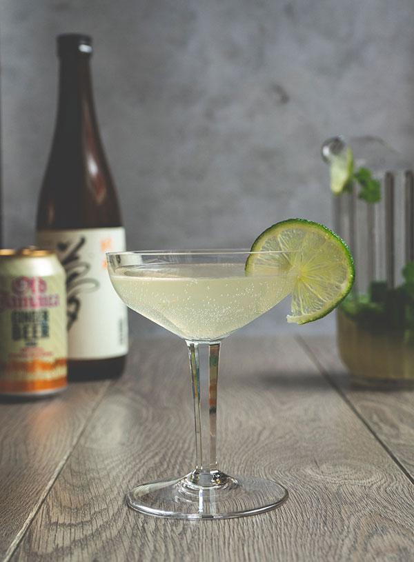 Een Japanese Mule in een cocktail glas met een schijfje limoen op de rand en de ingrediënten op de achtergrond.