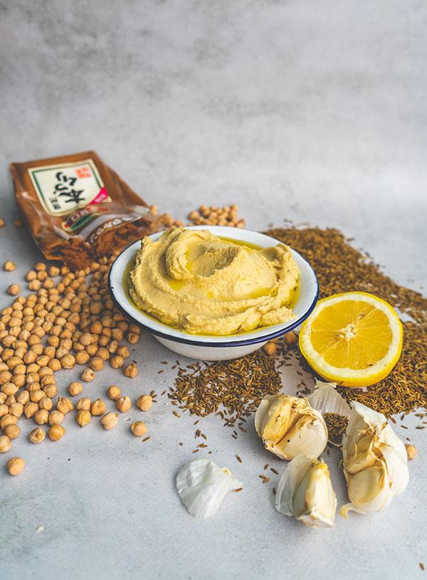 Een kom hummus omringt door de ingrediënten.