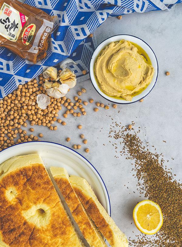 Een kom hummus met daarbij een Turks brood, omringt door de ingrediënten.