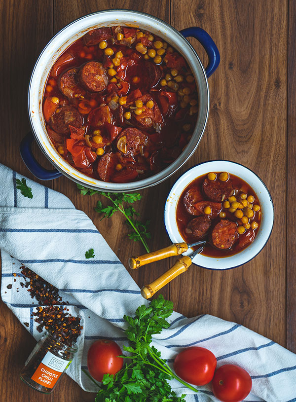 Een grote pan kikkererwten chorizo stoof met een kom gevuld met nog meer stoof erbij en de ingrediënten onderin de foto.