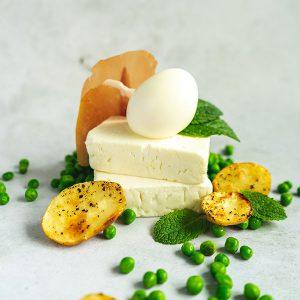 Twee blokken feta met een gekookt ei erop, omringt door doperwtjes, gebakken krieltjes en muntblaadjes.