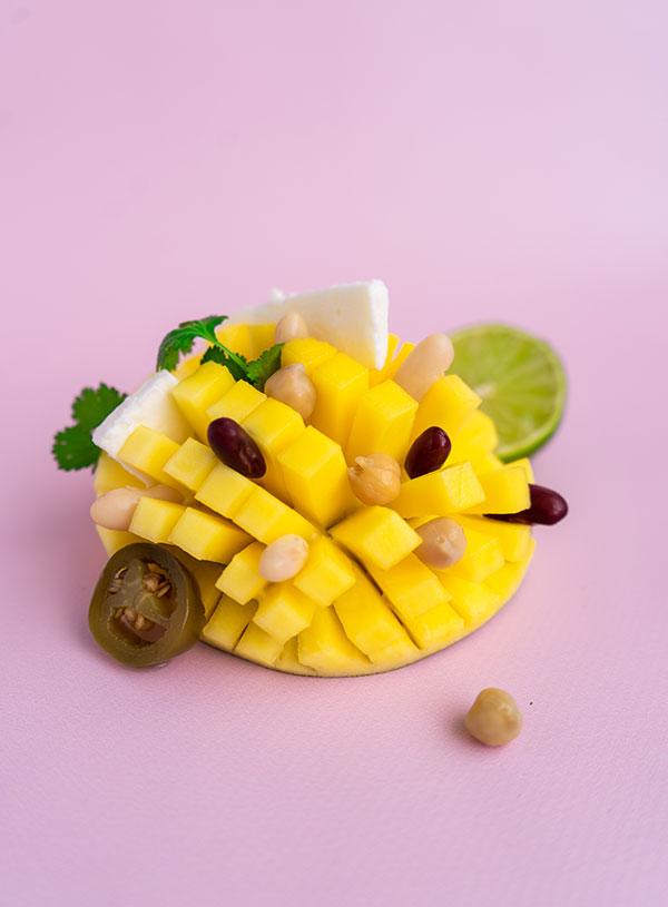 Een binnenstebuiten gekeerde en gesneden mango, met daarop de ingrediënten van de mango bonen salade