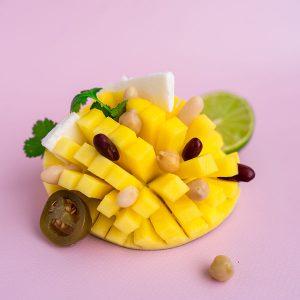 Een binnenstebuiten gekeerde en gesneden mango, met daarop de ingrediënten van de mango bonen salade.