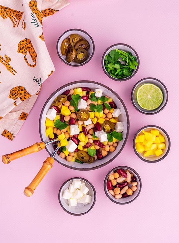 Een schaal mango feta en bonen salade met de ingrediënten in kleine kommetjes eromheen.