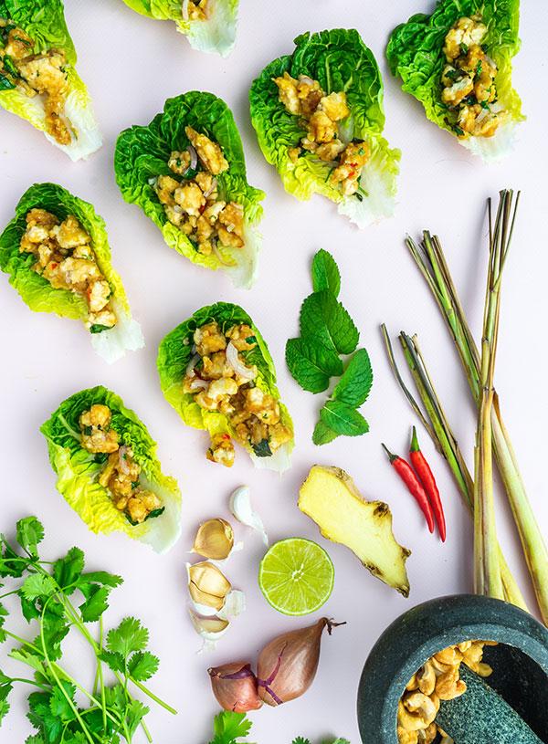Een closeup van blaadjes baby gem sla met tofu larb erin, omringt door de ingrediënten.