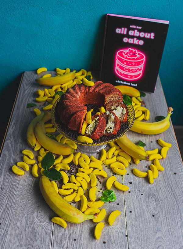 Een taartplateau met daarop bananen groene curry cake met peperkorrels omringt door Haribo bananenschuimpjes en echte bananen.
