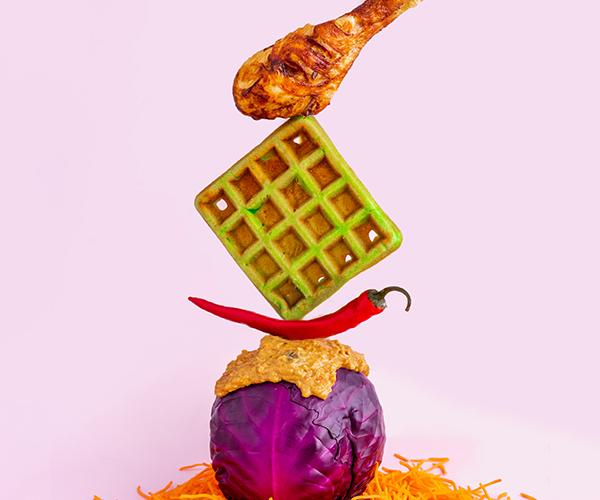 Een gebakken kippenpoot gebalanceerd op een groene wafel, gebalanceerd op een lombok, gebalanceerd op een hele rode kool met daarover heen pindasaus, tezamen op een bedje van geraspte wortel op een roze achtergrond