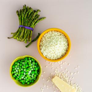 Een kommetje diepvriesdoperwtjes, een kommetje rijst, een bosje asperges en een blokje Parmezaan.