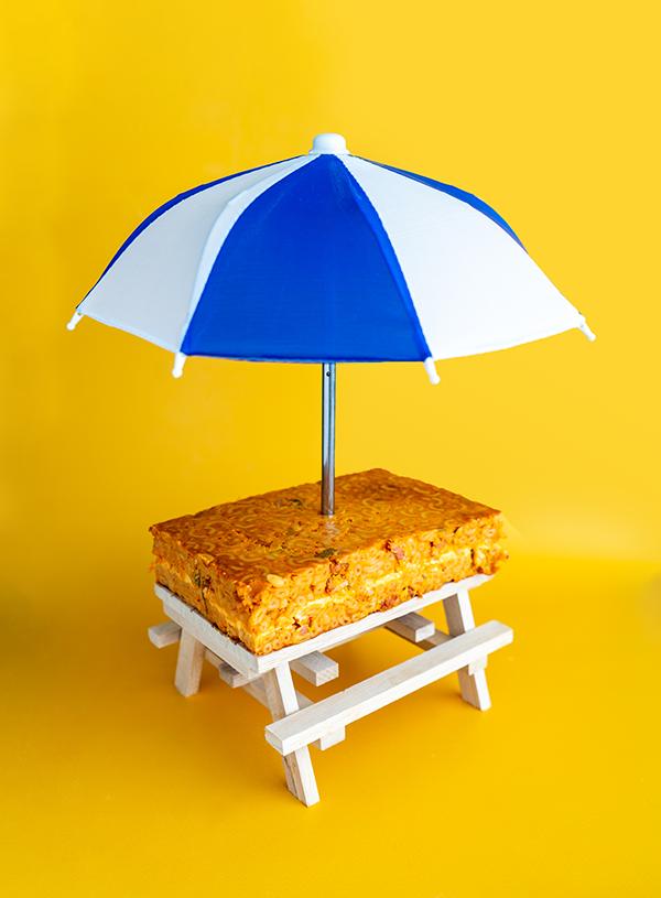 Een picknicktafel met daarop een blok macaroni met kaas met een parasol erin gestoken.