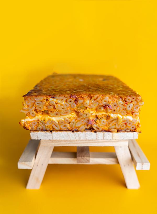 Een plak kimchi mac en cheese op een picknicktafeltje