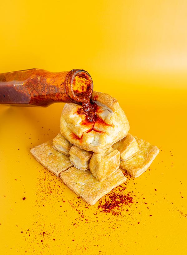 Een fles hot sauce die over oven gebakken krokante tofu blokken lekt