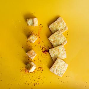 Blokken en plakken gebakken tofu op een gele achtergrond met gochugaru (Koreaanse pepervlokken) eromheen.