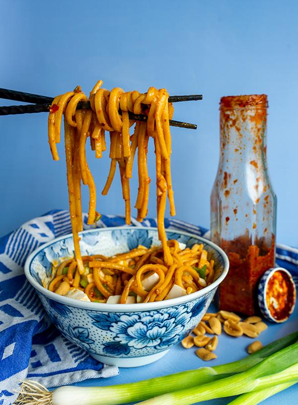 Een kom met pittige noedels met silken tofu met een fles mapo hot sauce ernaast.