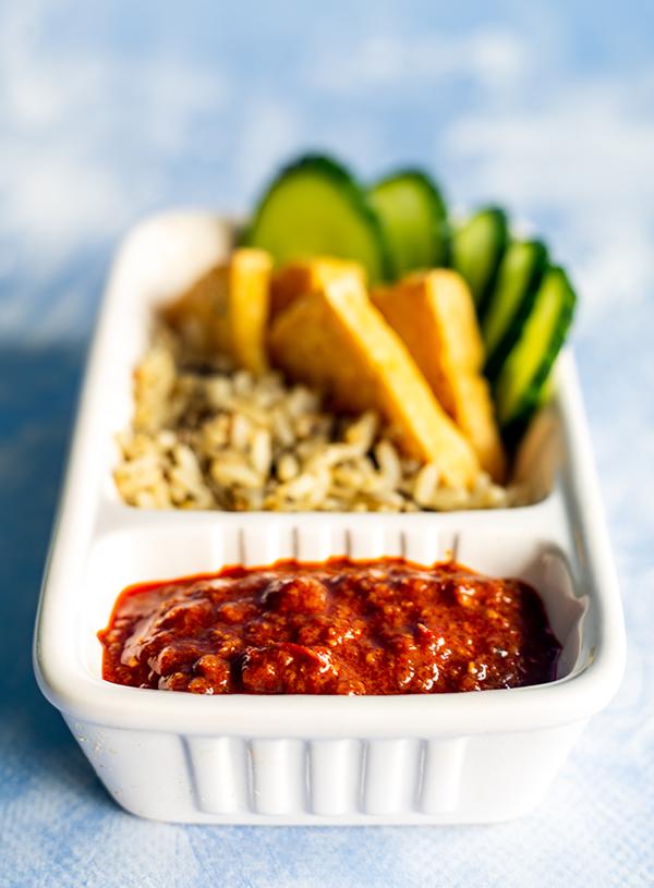 Een friet bakje met mapo tofu geïnspireerde hot sauce in het saus bakje en erbij rijst met tofu en komkommer