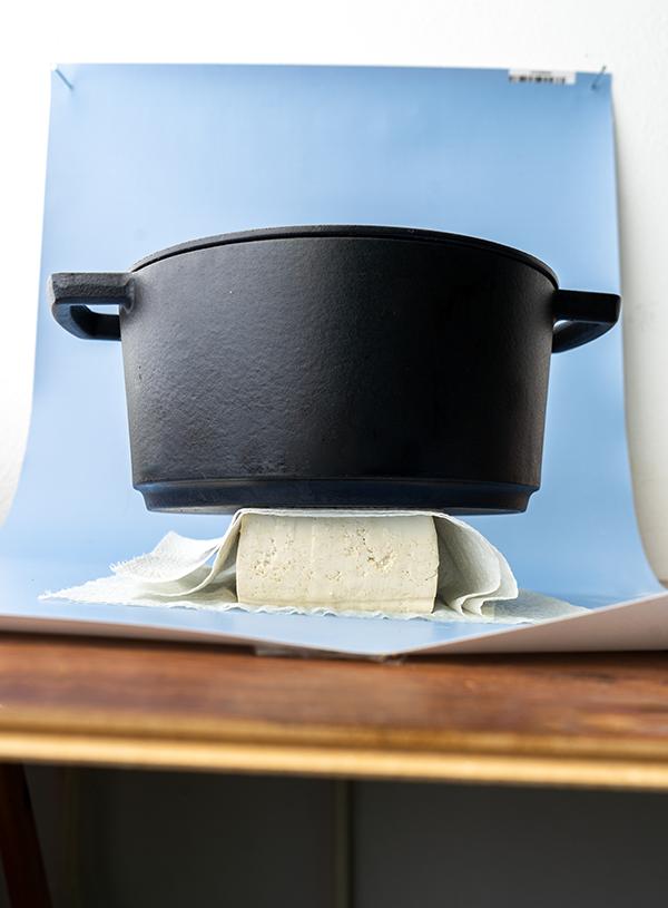 Een blok tofu tussen wat vellen keukenpapier, met daarop een zwarte gietijzeren pan gebalanceerd, op een blauwe achtergrond