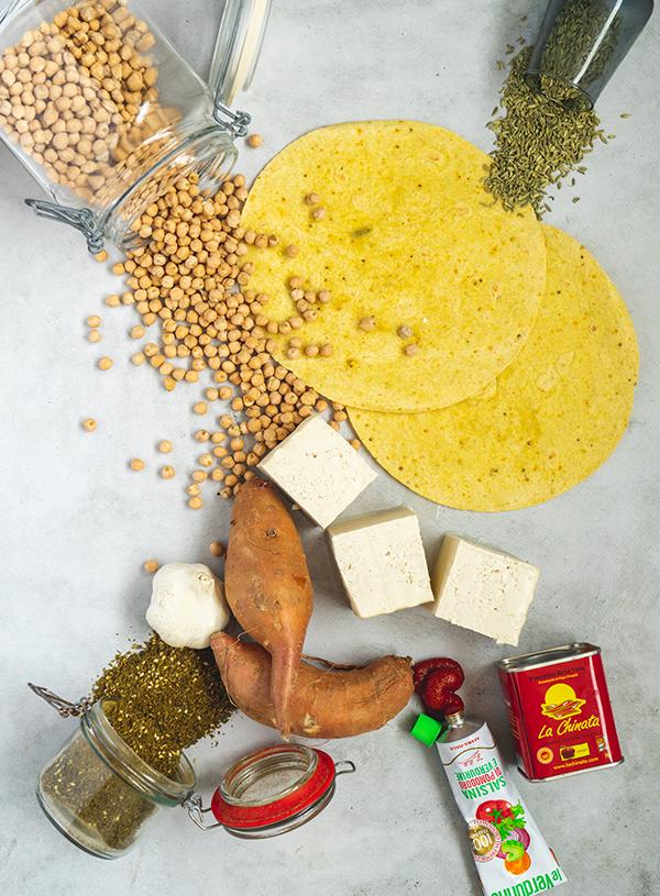 Een foto van rauwe ingrediënten met mais tortilla's en daaromheen gedrapeerd kikkererwten, tofu, zoete aardappel, diverse kruiden en tomatenpuree