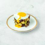 Een wit bord mte een gouden randje met daarop Boudin Noir hash met spruitjes en een gebakken ei met een zachte dooier op een wit marmeren achtergrond.