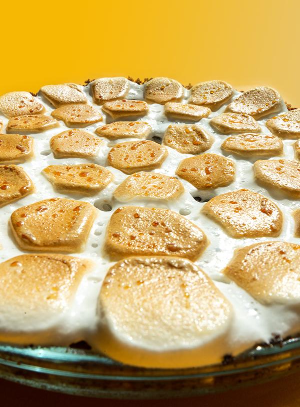 Een extreme close-up van gebrande marshmallows op een gele achtergrond.