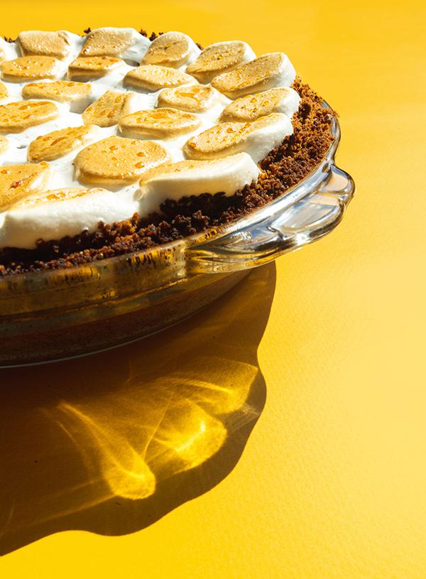 Een close-up van een smores pie bedekt met gebrande marshmallows op een gele achtergrond.