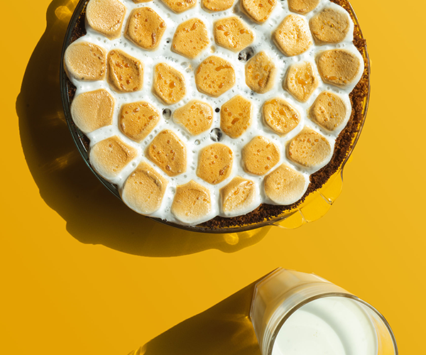 Een foto van bovenaf genomen van een smores pie bedekt met gebrande marshmallows met een glas melk ernaast op een gele achtergrond.