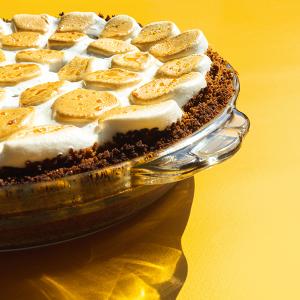 Een vierkante close-up van een smores pie bedekt met gebrande marshmallows op een gele achtergrond.