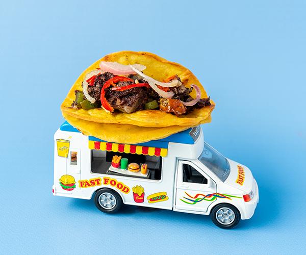Een miniatuur foodtruck met daarop een bloedworst taco op een blauwe achtergrond.