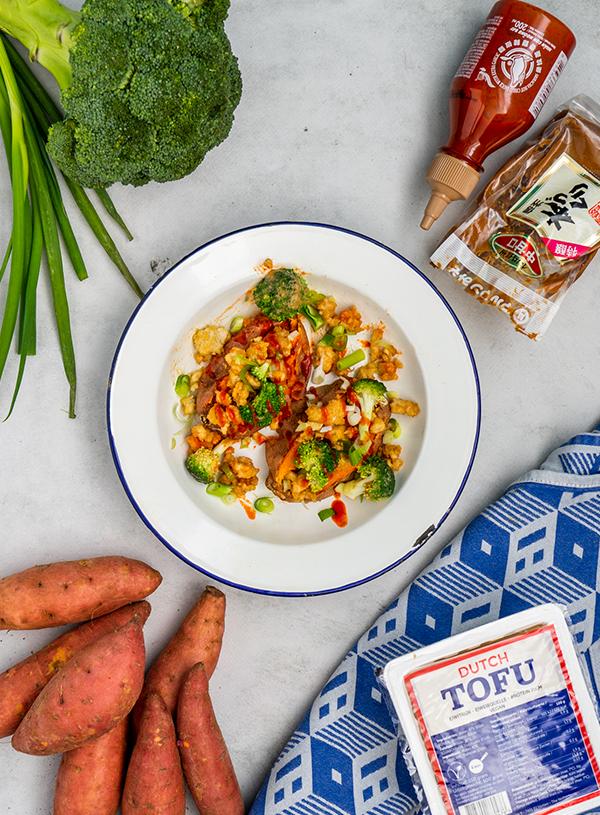 Een wit bord met een blauwe rand met daarop twee gepofte zoete aardappelen met broccoli en miso tofugehakt op een witte achtergrond met daar omheen broccoli, bosui, Sriracha, een pakje miso, zoete aardappelen, een pak tofu en een blauw geblokte theedoek.