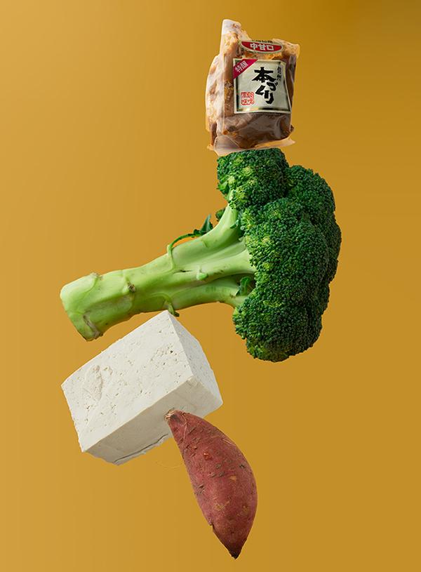 Een zoete aardappel met daarop balancerend een blok tofu, broccoli en een geopend pak miso op een gele achtergrond.