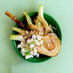Een vierkante foto van een groen bordje met daarop gekarameliseerde venkel met gebrokkelde feta en pijnboompitten en een bamboe vorkje, met daarna een klein kommetje met nog meer verkruimelde feta in een bruin kommetje op een groene achtergrond.