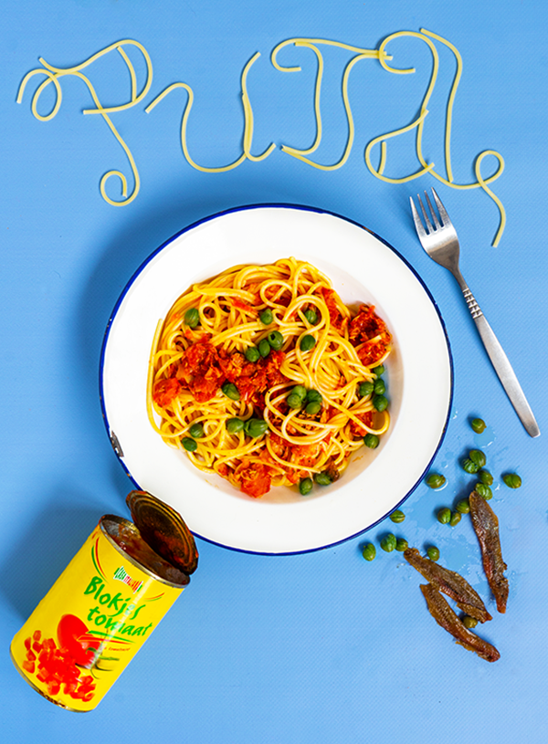 Een bord met spaghetti met rode saus en groene kappertjes op een wit bord op een blauwe achtergrond met ernaast een vork, een open blik tomaten, wat losse kappertjes en ansjovisfilets en het woord PUTA gespeld in spaghetti.