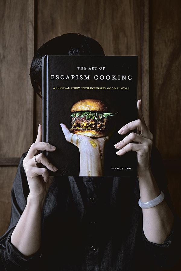 Foto van het boek The Art of Escapism Cooking van Mandy Lee, door haar vastgehouden met haar hoofd achter het boek verstopt.