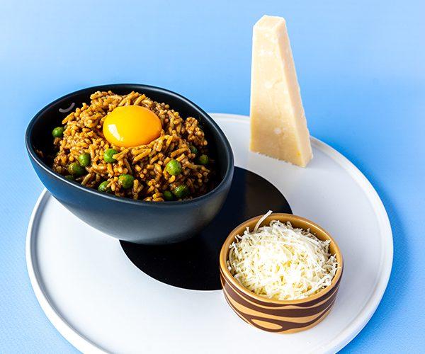 Verticale foto van Japanse curry risotto uit The Art of Escapism Cooking op een wit bord, met daarop een zwarte ovale kom met een rijst doperwten mengsel erin en daarop een eidooier, op het bord staat ook een klein kommetje met houtnerf opdruk met daarin geraspte Parmezaanse kaas en een torn van een afsneden punt Parmezaan.