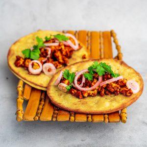 Een vierkante afbeelding van een mandje van bamboe op een beton achtergrond met daarop twee gefrituurde taco's met tofugehakt in rode saus, ingelegde sjalotten en korianderblaadjes.