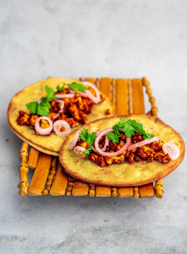 Een mandje van bamboe op een beton achtergrond met daarop twee gefrituurde taco's met tofugehakt in rode saus, ingelegde sjalotten en korianderblaadjes.