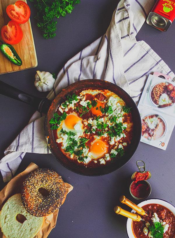 Een pan shakshuka met daaromheen de ingrediënten, een gesneden bagel en een theedoek