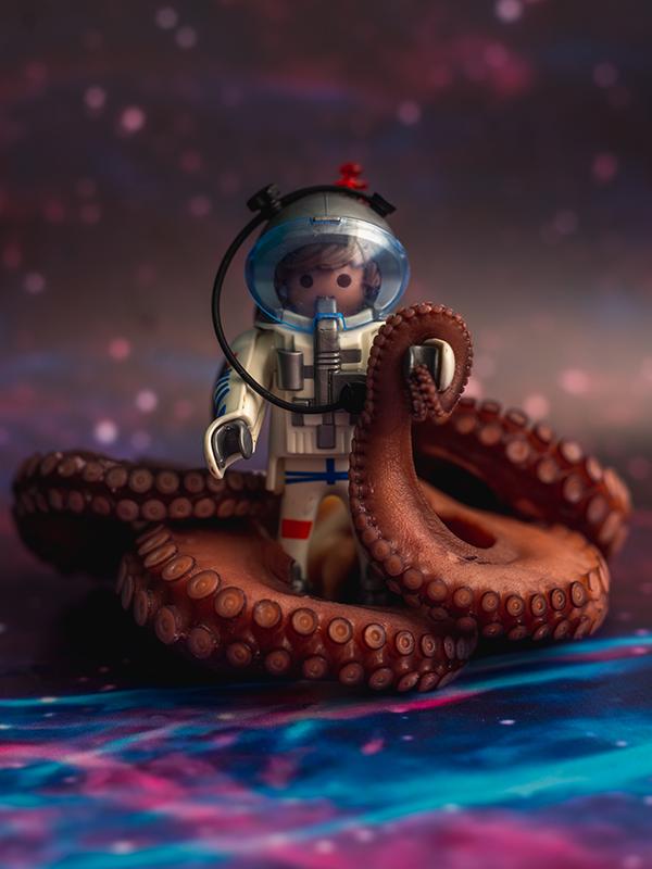 Een Playmobil astronaut omringt door gekookte rode tentakels van een octopus op een achtergrond alsof het zich in de ruimte afspeelt..
