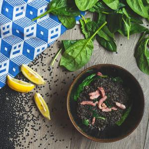 Een kom linzen soep met bacon en spinazie en daaromheen rauwe zwarte linzen, rauwe spinazie, partjes citroen en een blauw geblokte theedoek