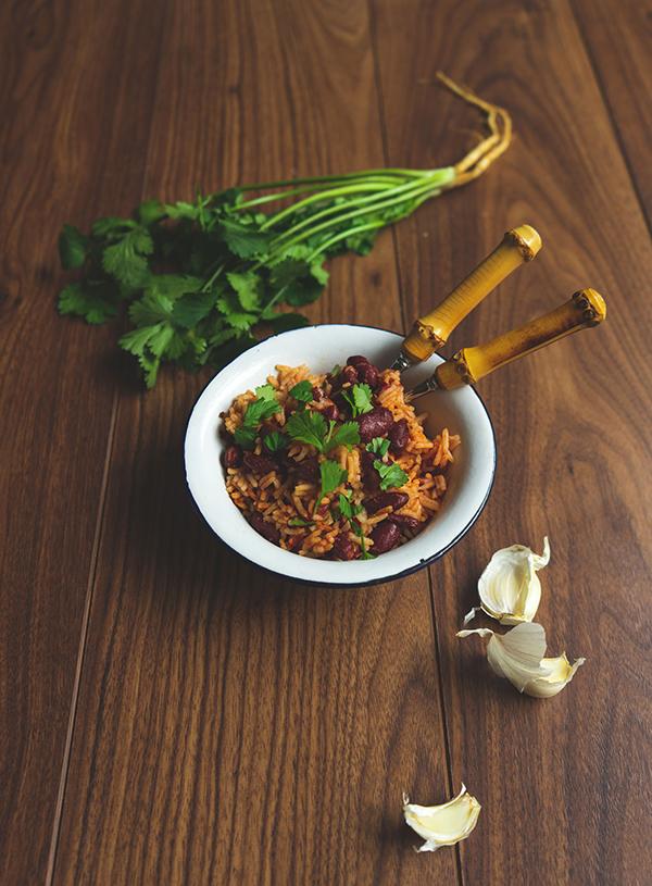 Een bord rijst met bonen met eromheen een paar van de ingrediënten